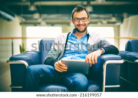 Smart businessman with touchpad sitting in office - stock photo