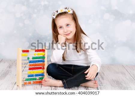 Smart dreaming young girl with abacus - stock photo