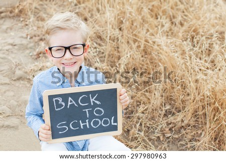 smart excited little boy in glasses holding chalkboard, ready for school, back to school concept - stock photo