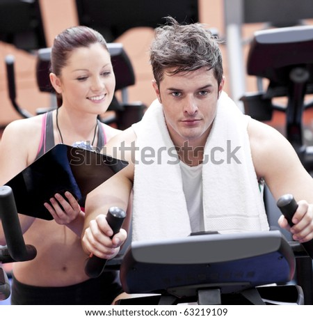 Smart female coach taking notes while her pupil is pedaling on a bicycle in a sport centre - stock photo