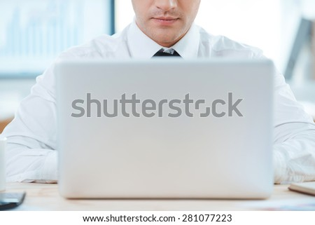 Smart gadget means smart solutions. Close-up of businessman working on laptop while sitting at his working place - stock photo
