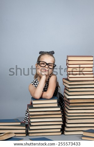 smart girl with a stack of books. Girl with glasses reading a book - stock photo