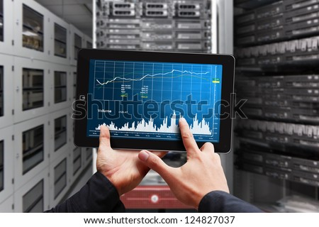 Smart hand press on digital tablet with graph report - stock photo