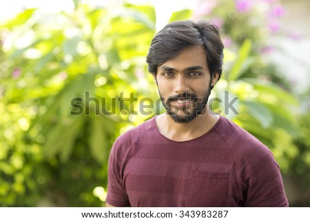 Smart happy Indian young man portrait in garden background. - stock photo