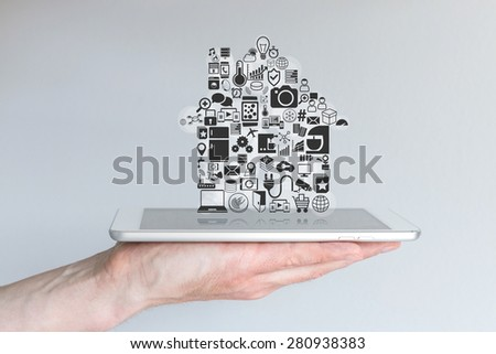 Smart home automation and mobile computing concept with male hand holding tablet - stock photo