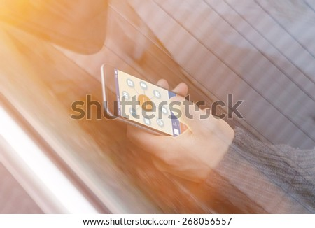 smart house device illustration with app icons. Man in the nature holding his smartphone with smart home app - stock photo