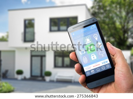 smart house, home automation, device with app icons. Man uses his smart phone with smarthome security app to unlock the door of his house. - stock photo