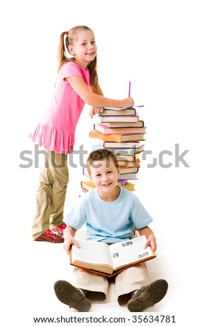 Smart lad sitting with open encyclopaedia and looking at camera on background of his friend standing by heap of books - stock photo