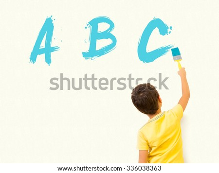 Smart little boy learning English and writing alphabet letters ABC with painting brush on wall background - stock photo
