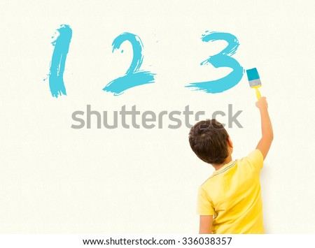 Smart little boy learning math and writing numbers 123 with painting brush on wall background - stock photo