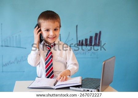 Smart little boy, working on computer, taking notes and speaking on the phone - stock photo