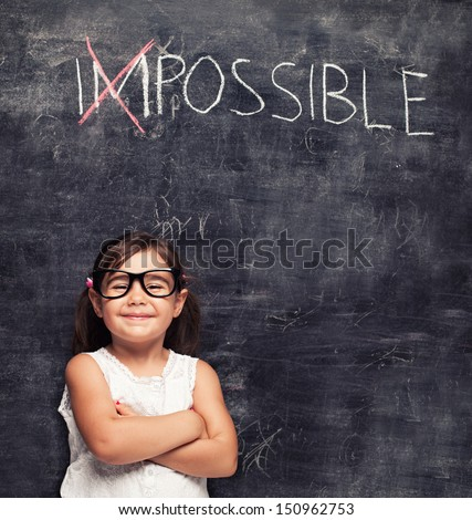 smart little girl smiling in front of a blackboard - stock photo
