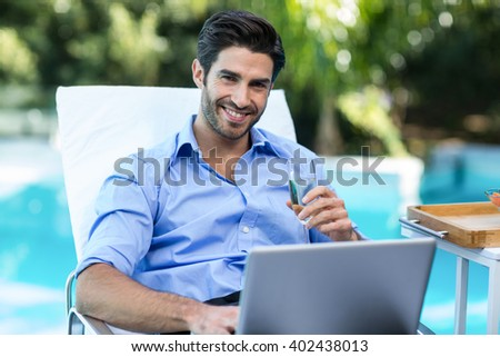 Smart man having champagne while using a laptop near pool - stock photo