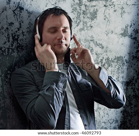 smart man leaning against a wall, listening to relaxing music - stock photo