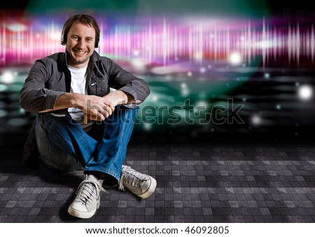 smart man sitting on the floor in a disco and listening to good music - stock photo