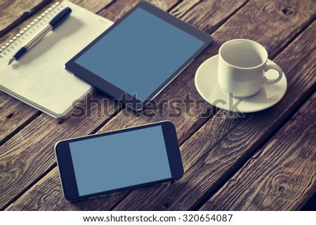 Smart phone and digital tablet devices on a desktop. Clipping paths included. - stock photo