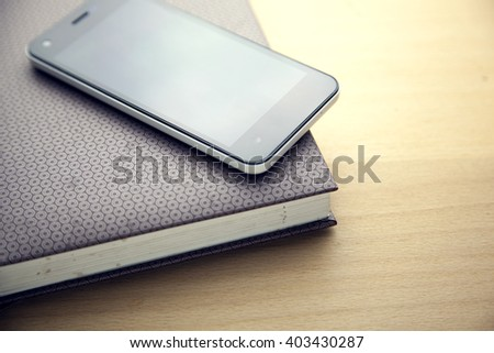 Smart phone and notepad on wooden background - stock photo