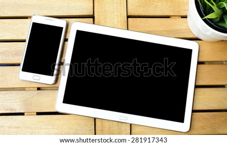 Smart phone and tablet pc with plant. Smart phone and tablet pc with green plant on wooden table. - stock photo