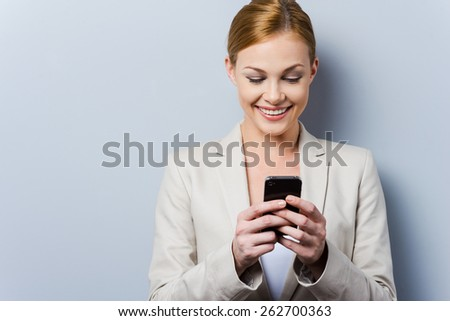 Smart phone for smart people. Beautiful young businesswoman holding mobile phone and smiling while standing against grey background - stock photo