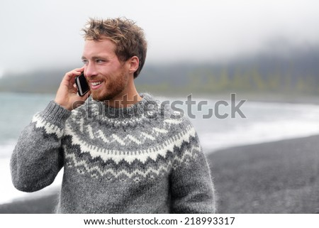 Smart phone man talking on smartphone walking on black sand beach on Iceland wearing Icelandic sweater. - stock photo