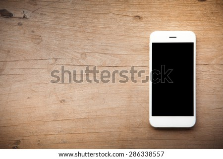 Smart phone on wooden background  - stock photo