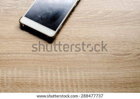 Smart phone on wooden table background - stock photo
