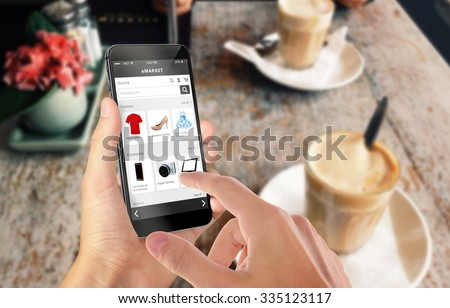 Smart phone online shopping in man hand. Desk with caffe in background. Buy clothes shoes accessories with e commerce web site - stock photo