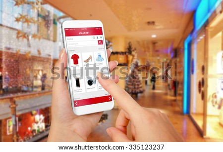 Smart phone online shopping in woman hand during Christmas. Shopping center in background. Buy clothes shoes accessories with e commerce web site - stock photo
