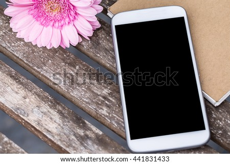 smart phone or cellphone with recycle notebook paper over grunge wooden table background. - stock photo
