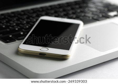 smart  phone rests at a right angle on the keyboard of a silver-and-black laptop. - stock photo
