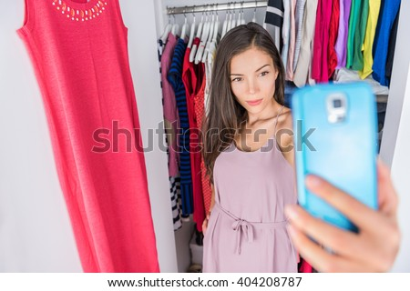 Smart phone selfie Asian woman in clothes closet of home bedroom or  store dressing room next to clothing rack. Shopping girl taking a photo of her outfit using smartphone fashion app. Social media. - stock photo