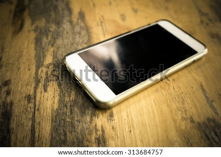 Smart phone with blank screen lying on wooden table- vintage filter effect - stock photo