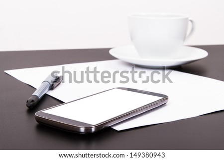 Smart phone with blank, white screen, ceramic coffee cup, pen and empty paper on wooden table, isolated on white background. - stock photo