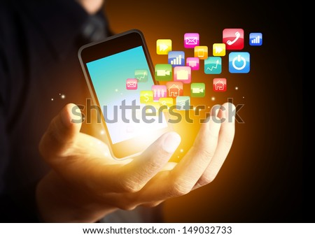 Smart phone with cloud of application icons in consumer hand - stock photo