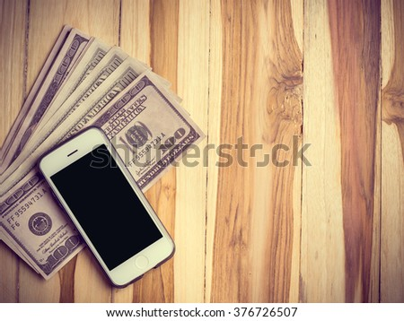 Smart phone with dollar banknotes on wood background. Making money online. select focus - stock photo