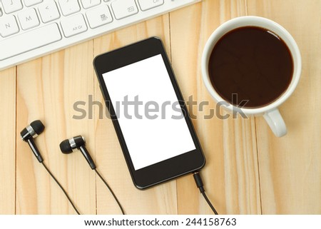 Smart phone with headphones, keyboard and coffee cup on wooden background - stock photo