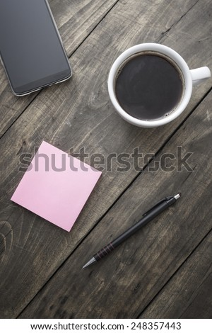Smart phone  with sticky note paper and cup of coffee on old wooden desk. - stock photo