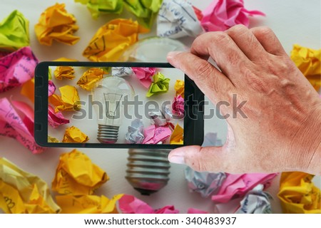 Smart phones photography a good idea concept with colorful crumpled paper and light bulbs. - stock photo