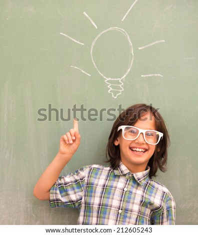 Smart schoolboy on school board with bulb for idea - stock photo