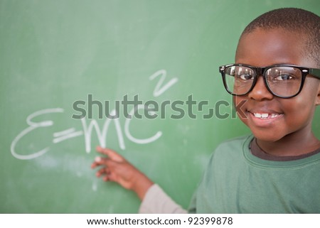 Smart schoolboy showing the mass-energy equivalence on a blackboard - stock photo