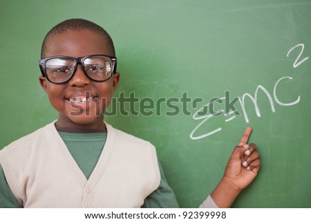 Smart schoolboy showing the the mass-energy equivalence formula on a blackboard - stock photo