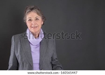 Smart senior woman with grey hair on grey background - stock photo