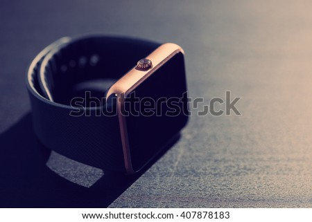 Smart watch lying on the surface with copy space on the right provided for text. Blue hipster tones - stock photo
