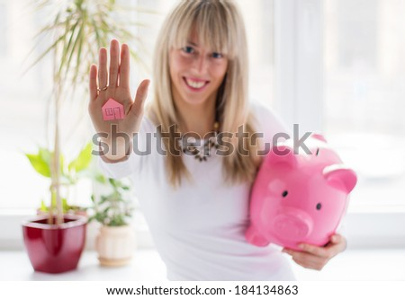 Smart woman saving money for the first down payment - stock photo