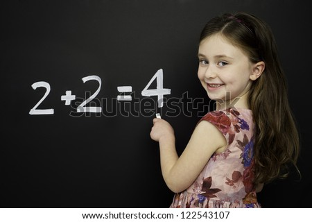 Smart young girl wearing a red dress writing math sums on a blackboard - stock photo