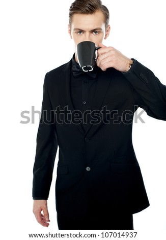 Smart young man drinking coffee in black cup over white background - stock photo