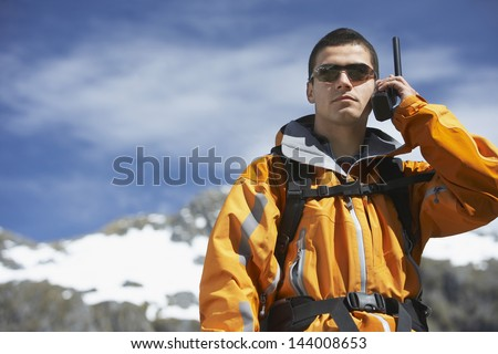 Smart young man using walkie talkie against blurred snow capped mountain - stock photo