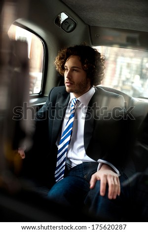 Smart young relaxed businessman traveling in taxi cab - stock photo
