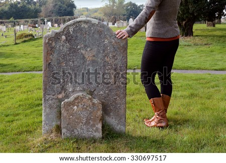 Smartly dressed woman rests her hand thoughtfully on a gravestone in a cemetery - stock photo