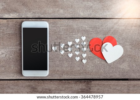Smartphone and hearts paper on wooden background. valentien or Sending love through social networks - stock photo